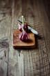 Two garlic bulbs on wooden kitchen board