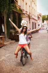 Happy young woman riding on bicycle with her boyfriend