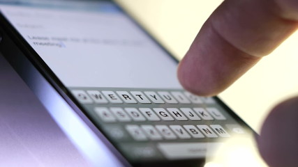 finger types out a text message on touch screen phone