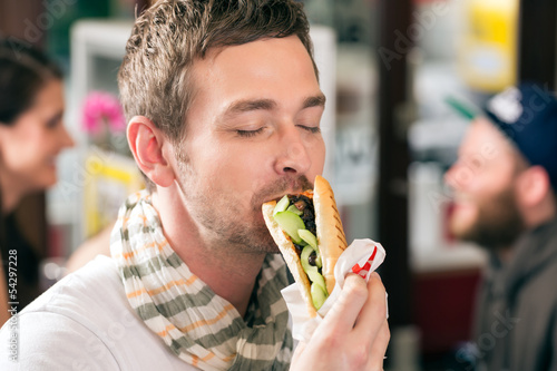 Customer eating Hotdog in fast food snack bar