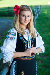 beautiful woman with red flower in her hair posing in Romanian t