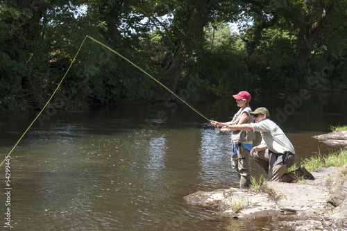 Fly fishing gillie instructing a pupil River Lyd Devon UK