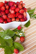 Wild strawberries in a small bowl, surrounded by leaves