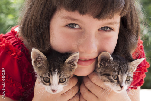 Little girl holding two cute kitten