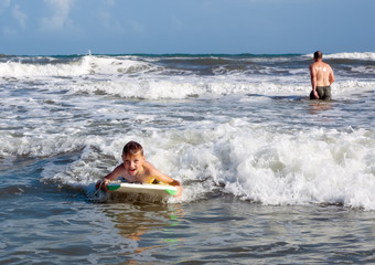 Joyful child on the board is racing with the wave. Bodyboarding