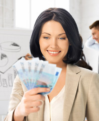 happy businesswoman with cash money in office