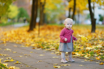 Adorable girl having fun on autumn day