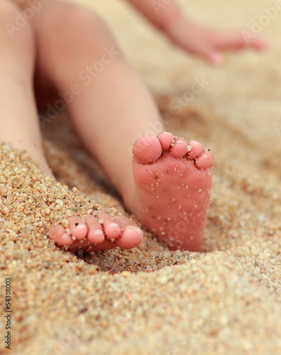 Baby feet lying on yellow beach sand