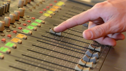 Hands adjusting gain sliders on mixing console