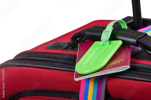 Passport and a luggage tag on suitcase