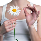 Young girl guesses on a chamomile flower. Young girl tears off p
