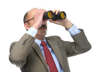 The businessman looks in the binoculars