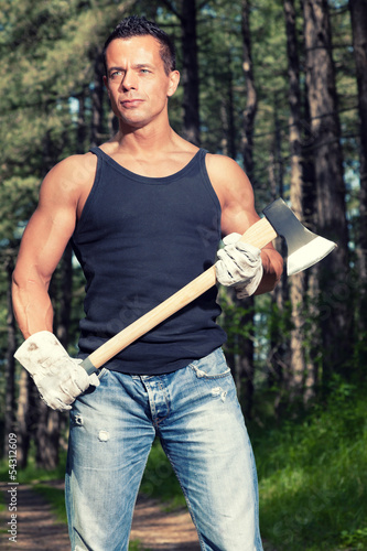 Muscled man with black shirt and axe in forest.