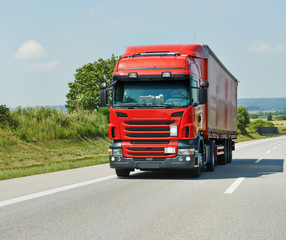 red lorry with trailer on highway