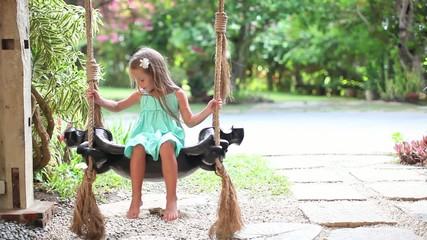 beautiful little girl swinging on a swing in a cozy lovely
