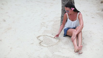 Woman sitting on beach and and drawing heart in the sand