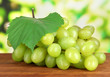 Ripe delicious grapes on table on bright background