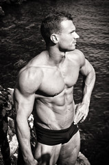 Black and white photo of attractive muscular young man