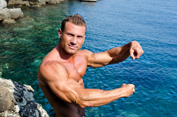 Handsome young bodybuilder by the sea showing arms