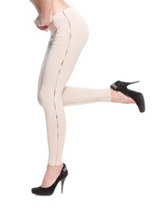 Close up of woman legs in fawn leggins and black shoes on white