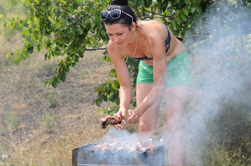 Attractive woman cooking meat on a barbecue