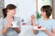 frau erzählt ihrer freundin etwas bei kuchen und kaffee