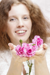 Young beautiful girl holding pink carnation flowers. Pretty smil