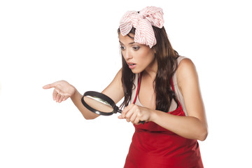 worried housewife looking through a magnifying glass