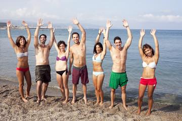 Menschen winken am Strand