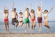 Sieben Personen springen am Strand