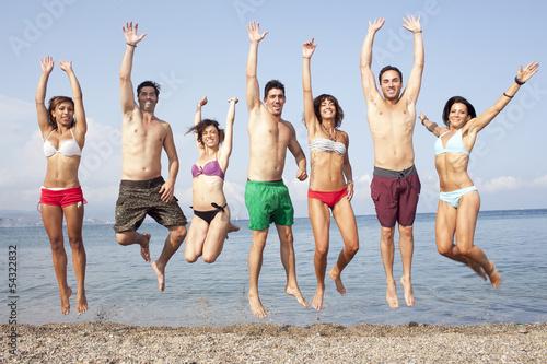 canvas print picture Sieben Personen springen am Strand
