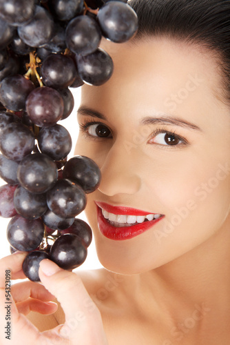 Beautiful sensual brunette eating grapes