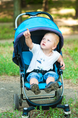 little boy in a pram on a walk in the park