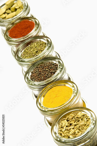 Herbs and spices in glass jars, isolated on white background