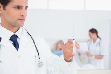 Handsome doctor holding syringe