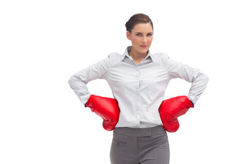 Businesswoman with hands on hips wearing boxing gloves
