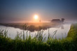 misty sunrise over river in farmland
