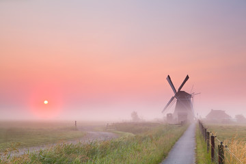 windmill and rising sun in fog