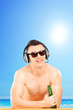 Smiling guy with headphones and sunglasses drinking beer, on bea