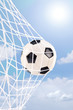 Soccer ball in a net against cloudy sky
