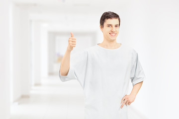 Smiling patient wearing hospital gown and giving thumb up, in a