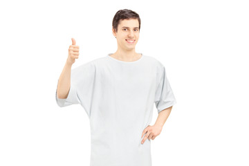 Smiling male patient wearing hospital gown and giving thumb up