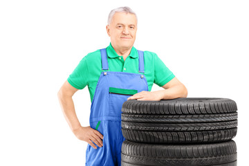 Smiling mature worker posing on car tires