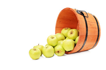 Studio shot of yellow apples in a wooden bucket