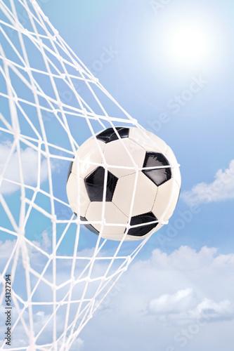 Soccer ball in a net against cloudy sky