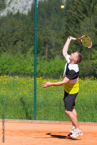 male tennis player hits the service ball