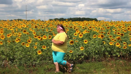 fitness - overweight woman running along field of sunflowers
