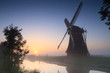 Dutch windmill at a foggy sunrise in the countryside