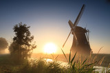 Dutch windmill at a foggy sunrise