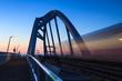 Train speeding over a bridge at dusk.